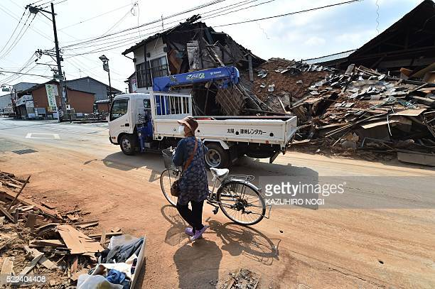 TOPSHOT A woman walks with her bicycle on a street beside collapsed houses in Mashiki Kumamoto prefecture on April 19 2016 More than 500 earthquakes...