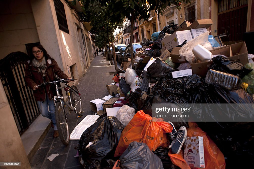 A woman walks with her bike past uncollected rubbish in a street of Sevilla on February 4, 2013. Rubbish collectors have been on strike in the municipality of Sevilla to protest against the austerity cuts imposed by the town hall.