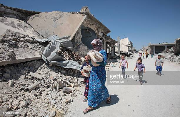 A woman walks with her children in the streets of the destroyed Syrian town of Kobane also known as Ain alArab Syria June 20 2015 Kurdish fighters...