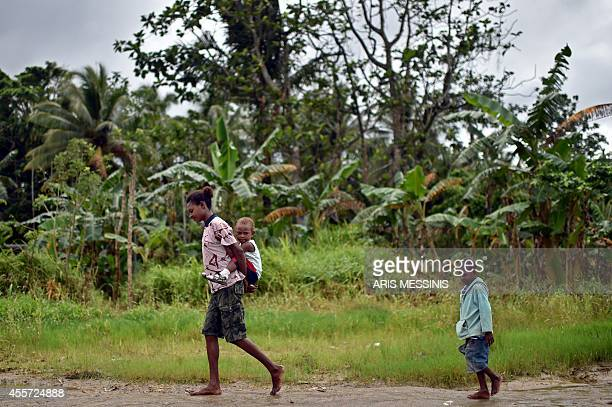 A woman walks with her children in the town of Kerema Papua New Guinea on September 5 2014 AFP PHOTO / ARIS MESSINIS