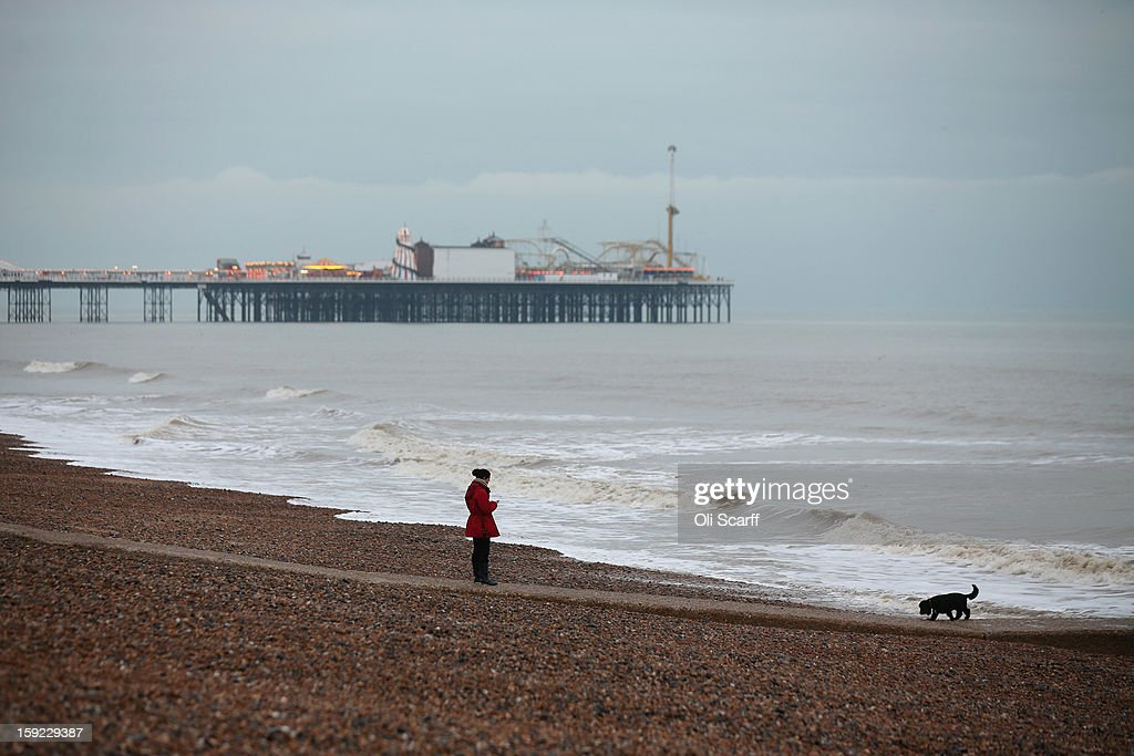A woman walks with her dog along Brighton beach on January 9, 2013 in Brighton, England.