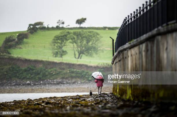 A woman walks with her dog along the stone coast of Bantry Bay on June 01 2017 in Bantry Ireland