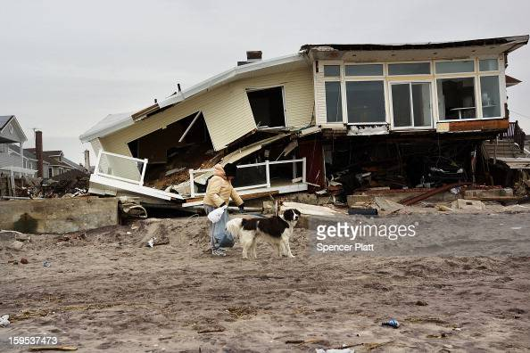 A woman walks with her dog by homes damaged by Hurricane Sandy along the beach in the Rockaways on January 15 2013 in New York City A $507 billion...