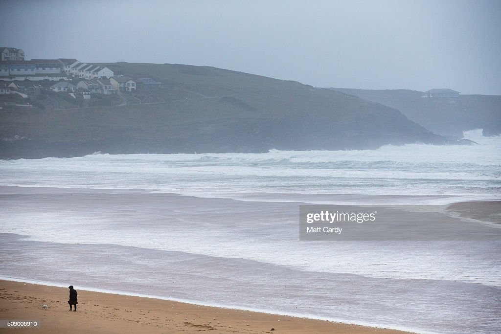 A woman walks with her dog on Fistral Beach in Newquay on February 8, 2016 in Newquay, England. Parts of the UK are currently being battered by Storm Imogen, the ninth named storm to hit the UK this season. Thousands of homes have been left without power and commuters hit by road and rail chaos as Storm Imogen batters the South with gale force winds and torrential rain.