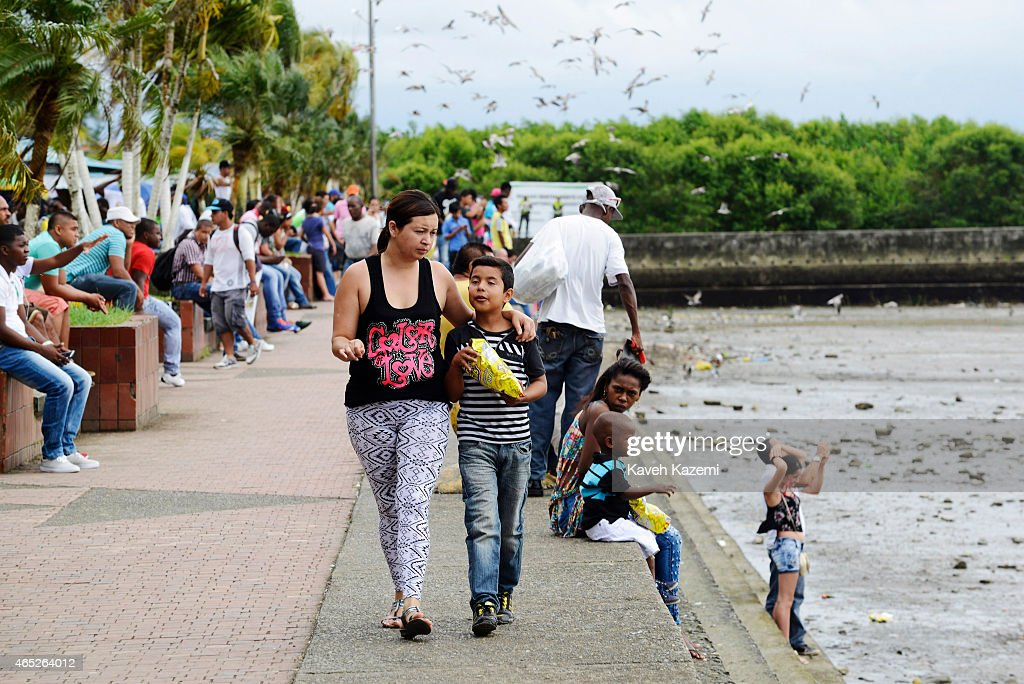 BUENAVENTURA COLOMBIA JANUARY 14 2015 A woman walks with her son on the seafront enjoying a late afternoon breeze on January 14 2015 in Buenaventura...