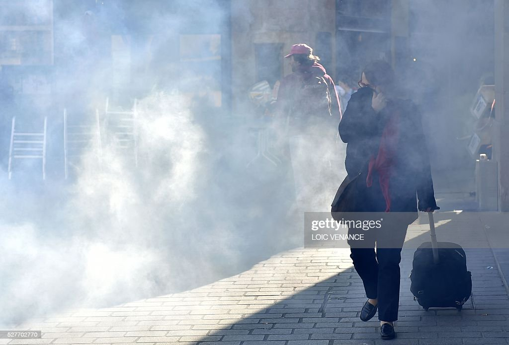 A woman walks with her suitcase past demonstrators during a protest against the government's planned labour law reforms in Nantes, western France, on May 3, 2016. High school pupils and workers protested against deeply unpopular labour reforms that have divided the Socialist government and raised hackles in a country accustomed to iron-clad job security. / AFP / LOIC