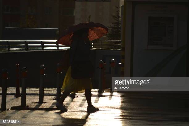 A woman walks with her umbrella as the sun illuminates a raindrenched road during a rainy autumn day in Ankara Turkey on September 26 2017 The...