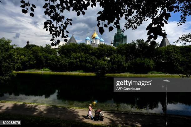 A woman walks with the stroller alongside a pond in front of the Novospassky monastery in Moscow on July 21 2017 / AFP PHOTO / Kirill KUDRYAVTSEV