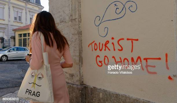 A woman walksby a graffiti opposing tourism written on a wall in Travessa da Ribeira Nova Cais do Sodre on October 31 2017 in Lisbon Portugal Large...