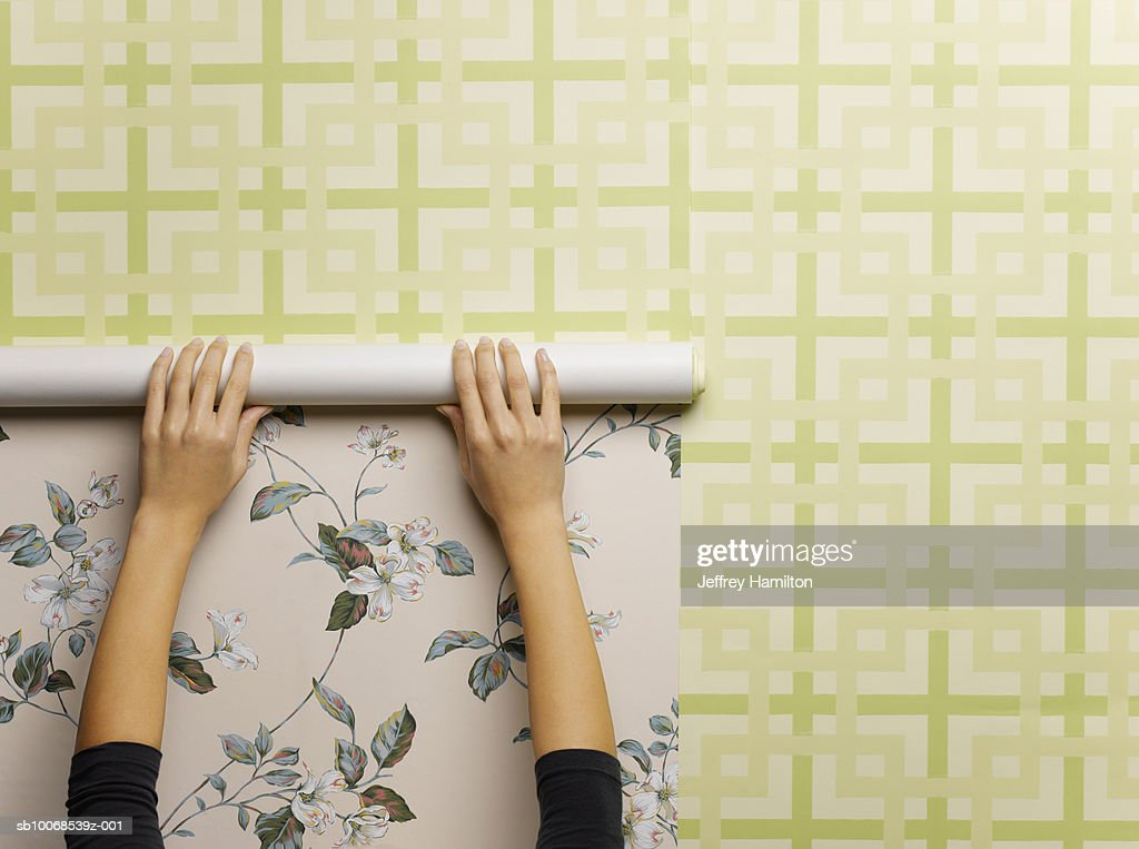 Woman wallpapering wall, close-up : Stock Photo