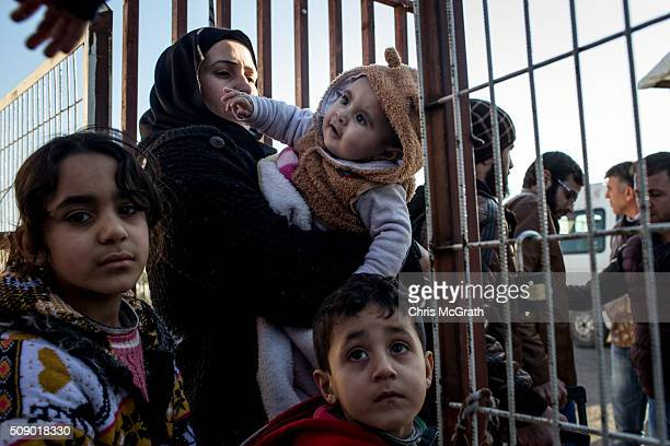 A woman wanting to leave Turkey carries her child through the border gate as a small number of Syrian refugees were allowed to return to Syria at the...