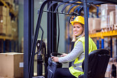 Beautiful young woman warehouse worker with forklift.