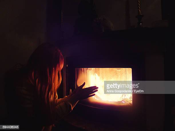 Woman Warming Hands By Fireplace At Home During Winter