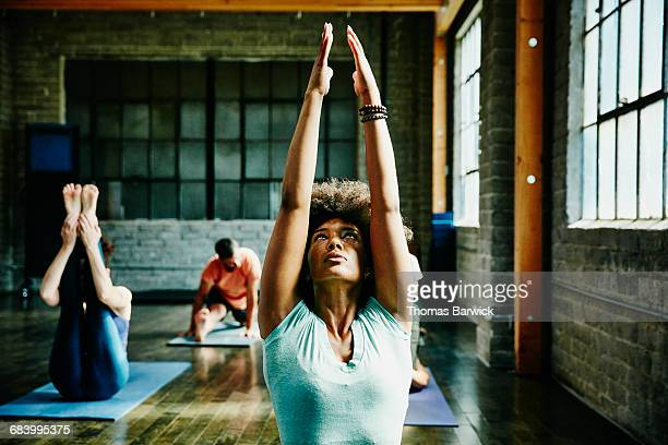 Woman warming up for yoga class in studio