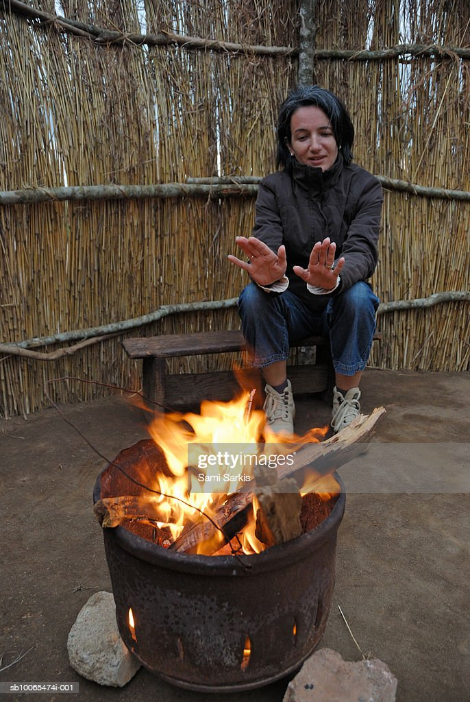 Woman warming up hands near brazier in hut