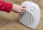 Woman warms her frozen hands near an electric fan heater at home. Selective focus.