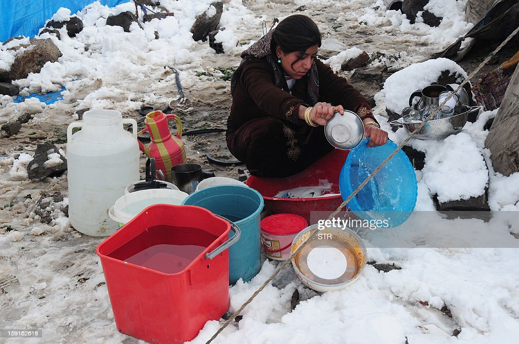A woman washes a basin at the Syrian refugee camp 5km from Diyarbakir, on the the way between Diyarbakir and Mardin, after snowfall, on January 9, 2013. The refugees faced further misery due to increasing shortages of supplies, low temperatures, and snowfall.