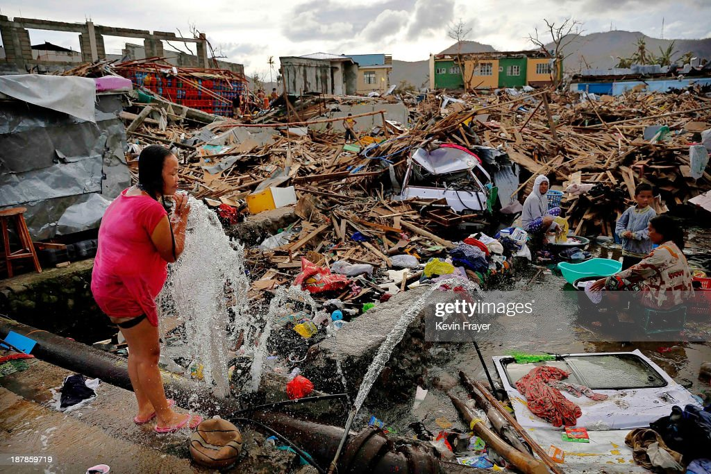 A woman washes amid scenes of devastation in the aftermath of Typhoon Haiyan on November 13, 2013 in Tacloban, Leyte, Philippines. Typhoon Haiyan, packing maximum sustained winds of 195 mph (315 kph), slammed into the southern Philippines and left a trail of destruction in multiple provinces, forcing hundreds of thousands to evacuate and making travel by air and land to hard-hit provinces difficult. Around 10,000 people are feared dead in the strongest typhoon to hit the Philippines this year.