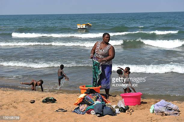 A woman washes clothes as children play along the Saga beach at Lake Malawi on July 17 2011 Lake Malawi remains unspoilt and one of Malawi's' biggest...