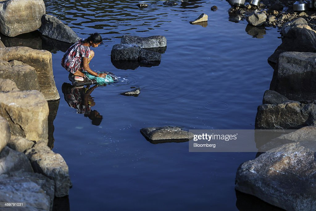 A woman washes clothes at a pond in Kainad, Maharashtra, India, on Saturday, Dec. 21, 2013. The construction of 600,000 kilometers (373,000 miles) of country roads, addition of 327 million rural phone connections and a rise in literacy to record levels since Prime Minister Manmohan Singh took office in 2004 has helped double the growth rate of Indias food output. Photographer: Dhiraj Singh/Bloomberg via Getty Images