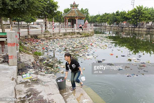 A woman washes clothes in a polluted river March 23 2008 in Guiyu China Since the late 1980's ewaste from developed countries has been imported to...
