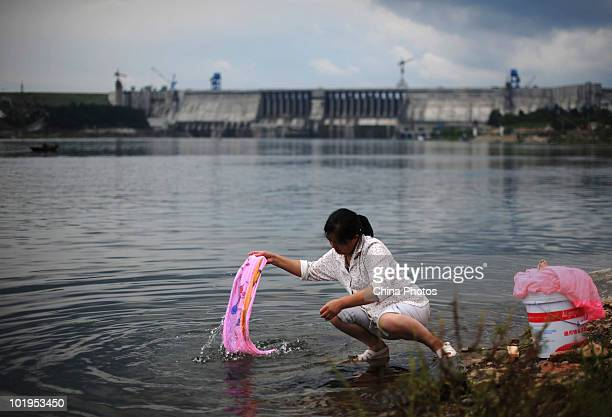 A woman washes clothes near the Danjiangkou Reservoir Dam on June 9 2010 in Danjiangkou of Hubei Province China Mass migration has been started in...