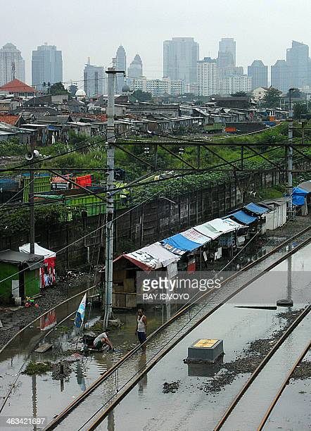 A woman washes clothes using floodwaters along train tracks in downtown Jakarta on January 18 2014 Indonesia is regularly affected by deadly floods...