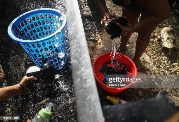 A woman washes clothes with water funneled from a mountain stream nearly one month after Hurricane Maria struck on October 19 2017 in Utuado Puerto...