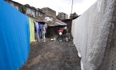 A woman washes dishes in the slum of Mathare one of the poorest slums in Nairobi on May 28 2014 Mathare is the second largest slum in Kenya with an...