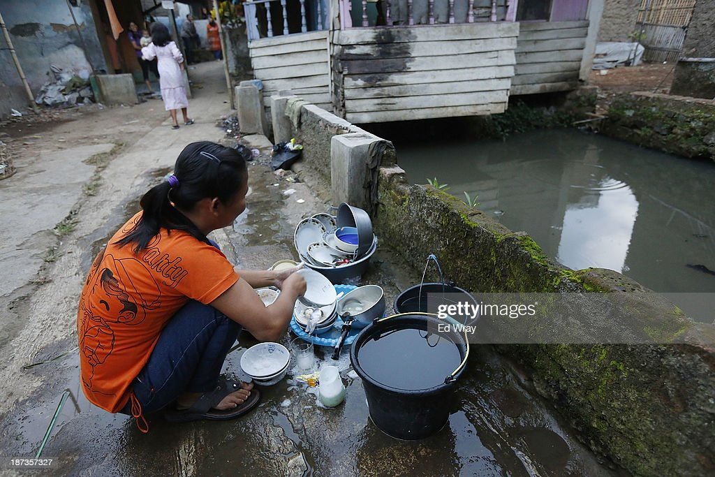 A woman washes dishes using water from the heavily polluted Citarum river in the town of Majalaya, a major textile producer on November 7, 2013 in Majalaya, Indonesia. The effects of domestic and industrial waste from factories along the river have prompted two leading environmental groups, Green Cross of Switzerland and the Blacksmith Institute, to name the Citarum river as one of the earth's 10 most polluted places in their annual report.