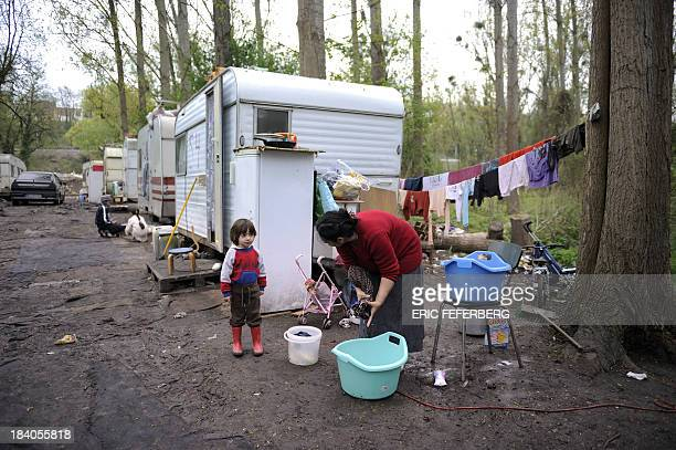 A woman washes her clothes near a caravan on April 5 2011 in the MoulinGalant camp in CorbeilEssonnes outside Paris where about 70 Roma families live...