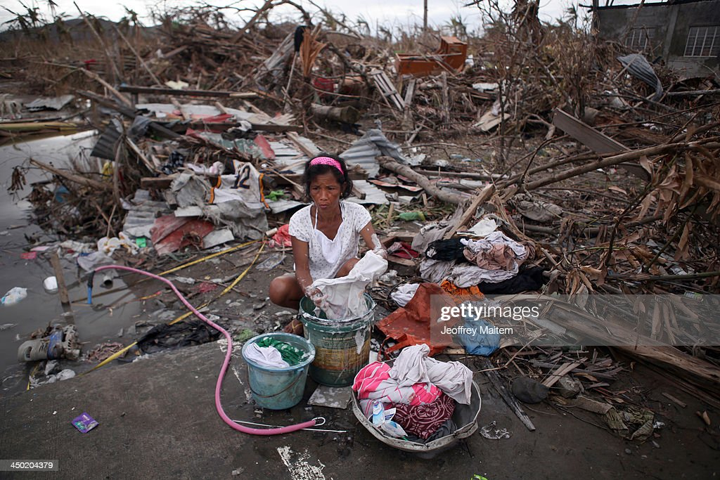 A woman washes her clothes on November 17 2013 in Tanauan Leyte Philippines Typhoon Haiyan which ripped through Philippines on November 9 has been...