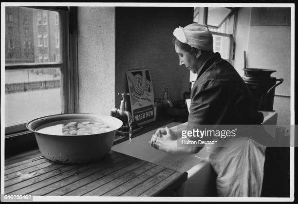 A woman washes her hands before handling a tub full of food A sign near the sink says to 'Wash Now'