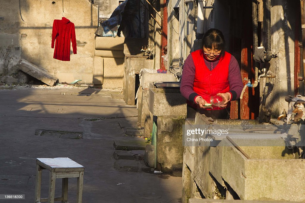 A woman washes wares in front of an old house at the North Bund on February 19, 2012 in Shanghai, China. According to local media, the North Bund area will be reconstructed as a international shipping and financial zone, a modern commercial and high-end residential area, and recreation center.