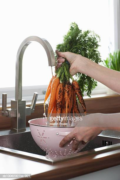 Woman washing carrots at kitchen sink, close-up of hands