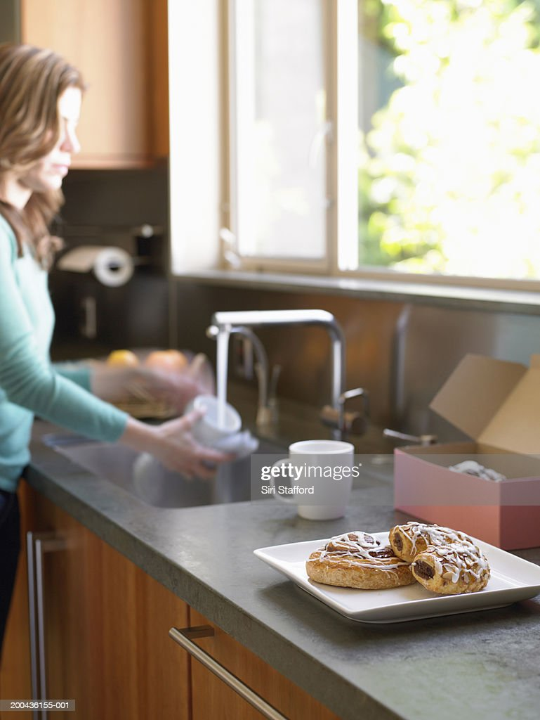 Woman washing cup in kitchen, baked goods on counter : Stock Photo