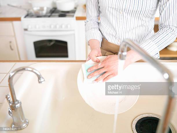 Woman washing dishes in kitchen, mid section, elevated view