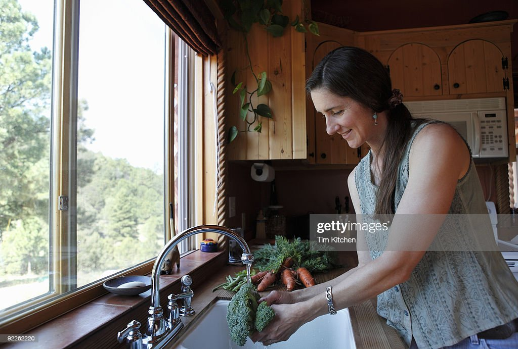 Woman washing fresh broccoli in sink in kitchen : Stock Photo