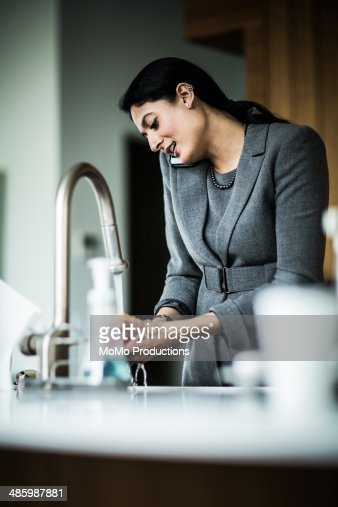 woman washing fruit in sink