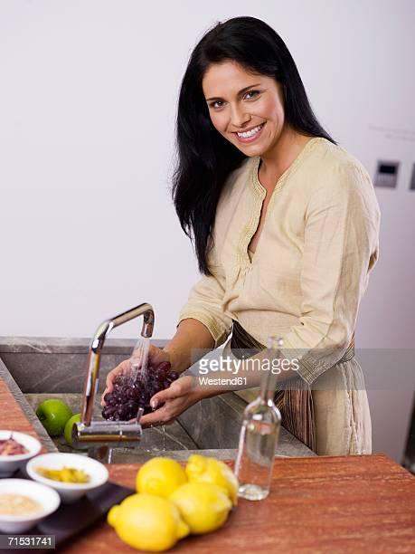 Woman washing grapes at kitchen sink, smiling
