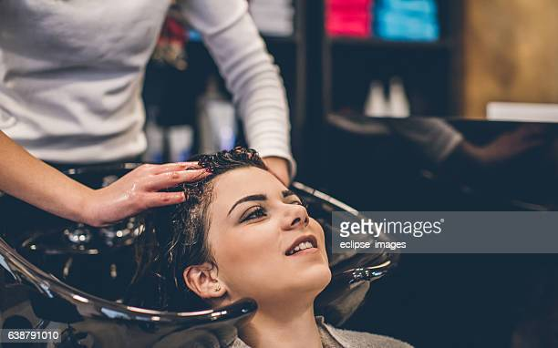 Woman washing hair at hairdressers