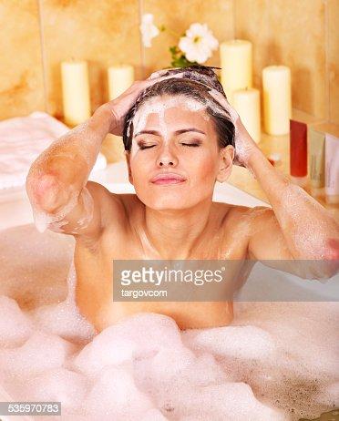 Woman washing hair by shampoo : Stock Photo