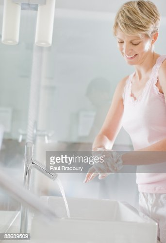 Woman washing hands in the bathroom : Stock Photo