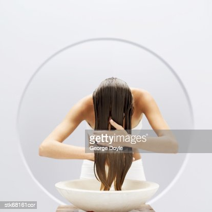 woman washing her hair in a basin : Stock Photo