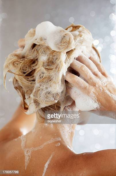Woman washing her hair in a shower.