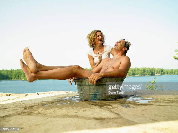 Woman Washing Man Outdoors