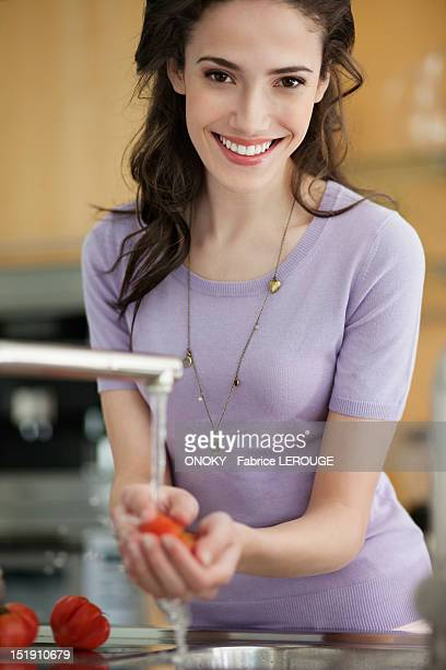 Woman washing tomatoes in the kitchen