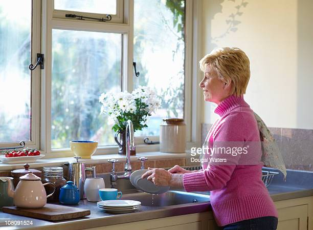 Woman washing up in kitchen.