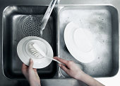 Woman washing up plate at sink, close-up