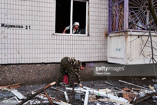 A woman watches a a man picks up an object from the floor after the area was hit by artillery fire on February 4 2015 in Donetsk Ukraine Artillery...